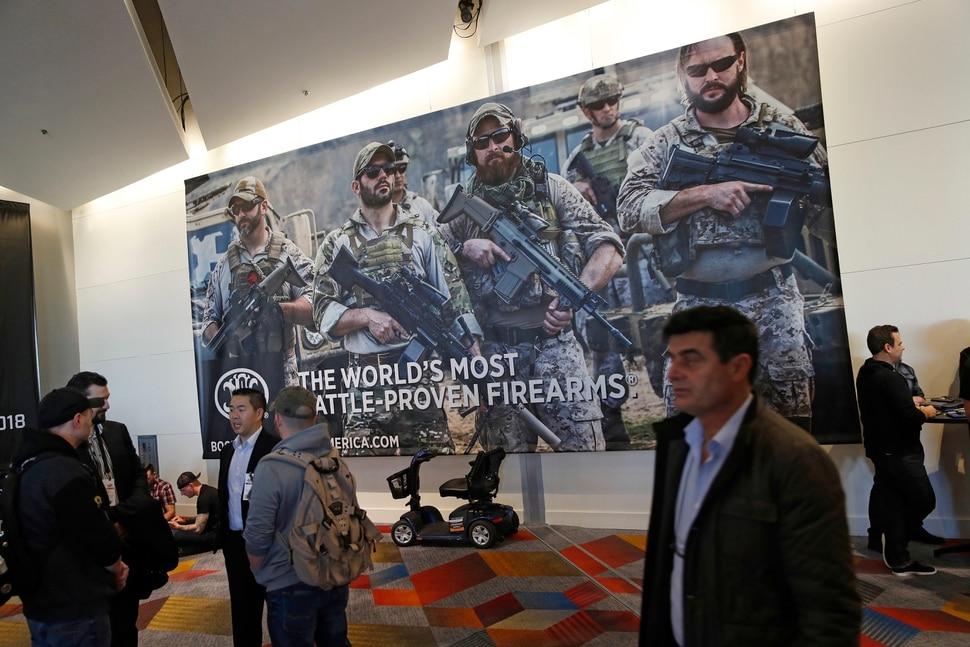 People walk through halls outside of the SHOT Show gun show Wednesday, Jan. 24, 2018, in Las Vegas. (AP Photo/John Locher)