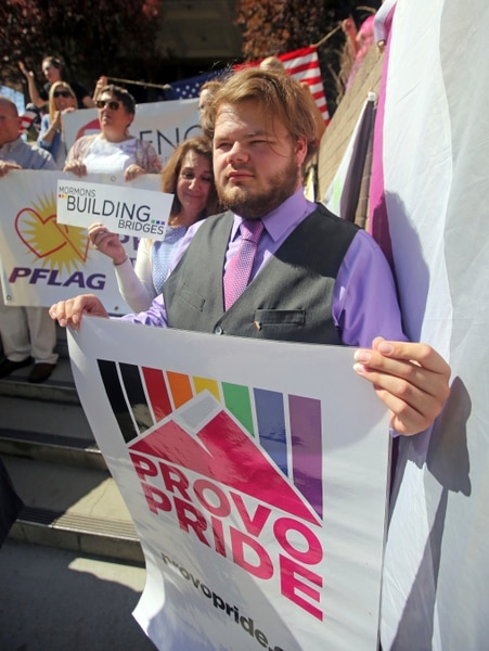 People hold signs during a news conference to discuss the America's Freedom Festival's decision Thursday, June 14, 2018, in Provo, Utah. LGBT groups that were denied requests to participate in a July 4 parade that is part of America's Freedom Festival in Provo spoke out Thursday about being rejected even after festival organizer and Provo city officials signed a nondiscrimination deal. (AP Photo/Rick Bowmer)