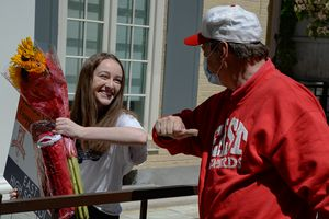 (Francisco Kjolseth  |  The Salt Lake Tribune) East High senior Erica Stringham gets an elbow bump from one of her teachers, Mr. Frank Langheinrich who teaches photography as she gets a home visit from a school team of teachers and fellow students as a way to celebrate the school seniors on Thursday, May 7, 2020.
