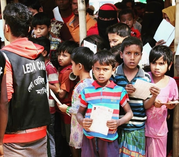 In a Rohingya refugee camp in Bangladesh, children waiting for meals show their government-issued registration cards. Photo by Sarah Franklin