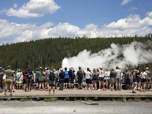 (Janie Osborne | The New York Times) Visitors crowd a boardwalk to view Old Faithful geyser at Yellowstone National Park in Wyoming on July 6, 2021. The park had more than 920,000 recreational visits in August 2021, surpassing its busiest August on record in 2017, when crowds came out to watch the solar eclipse.