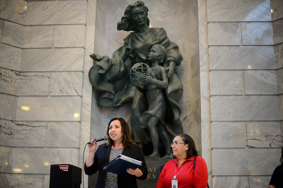 (Trent Nelson | The Salt Lake Tribune) Rep. Angela Romero, D-Salt Lake City and Rep. Rebecca Chavez-Houk, D-Salt Lake City, speak under a statue dedicated to Immigration and Settlement at a rally at the State Capitol building in Salt Lake City to remind Senator Hatch and Senator Lee that DACA is #HereToStay, Thursday August 31, 2017.