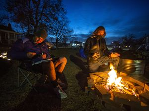 (Rick Egan | The Salt Lake Tribune) Bryan Dax Bilanzich (left) sits by the fire along with Darin Mann (right), where a group of people experiencing homelessness have been camping on Mann's front lawn for the past week, on Thursday, Jan. 21, 2021.