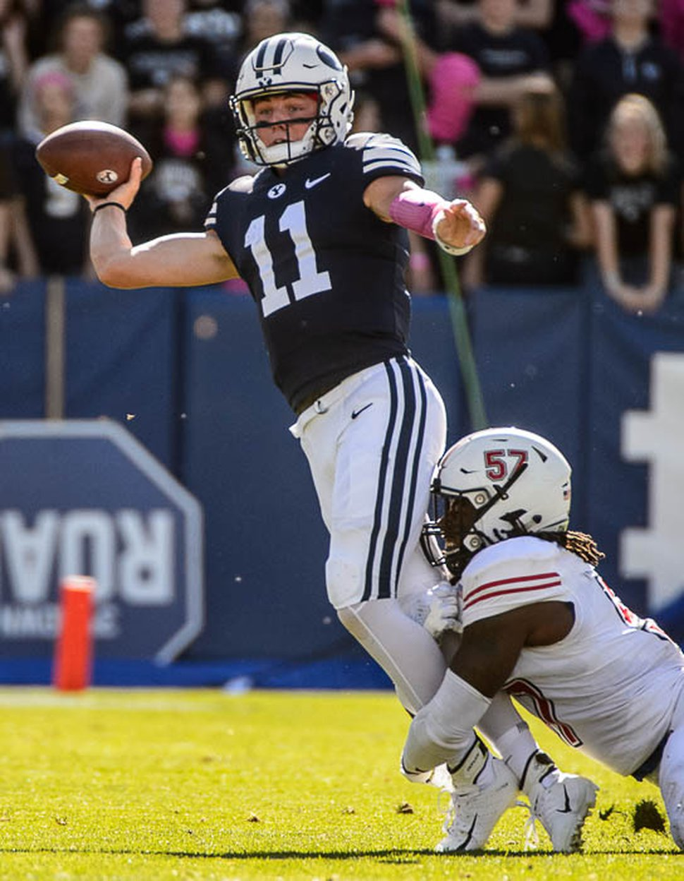 (Trent Nelson | The Salt Lake Tribune) Brigham Young Cougars quarterback Zach Wilson (11) throws the ball away as he's brought down by Northern Illinois Huskies linebacker Kyle Pugh (57) as BYU hosts Northern Illinois, NCAA football in Provo, Saturday Oct. 27, 2018.