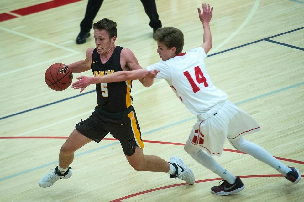 (Chris Detrick | The Salt Lake Tribune) Davis' Josh SandersÊ(5) runs past East's Brennan Hall (14) during the game at East High School Thursday, December 14, 2017.