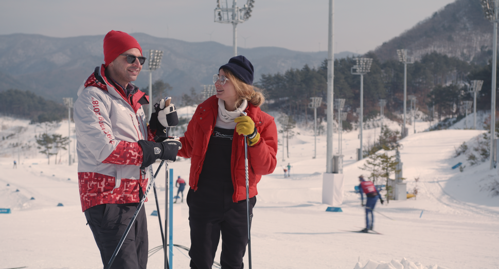 (Photo courtesy of IFC Films) Nick Kroll, left, plays Ezra, a volunteer dentist at the PyeongChang games, and Alexi Pappas, plays Penelope, an Olympic cross-country skier, in the romantic comedy Olympic Dreams, filmed on location at the 2018 Winter Olympics. It opens Friday, Feb. 21, 2020, at the Broadway Centre Cinemas in Salt Lake City.