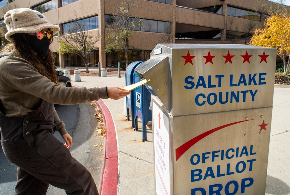 (Rick Egan | The Salt Lake Tribune) Evelyn Beguiristain drop her ballot in the vote-by-mail ballot drop box at the Salt Lake County Government Center on Monday, Oct. 19, 2020.