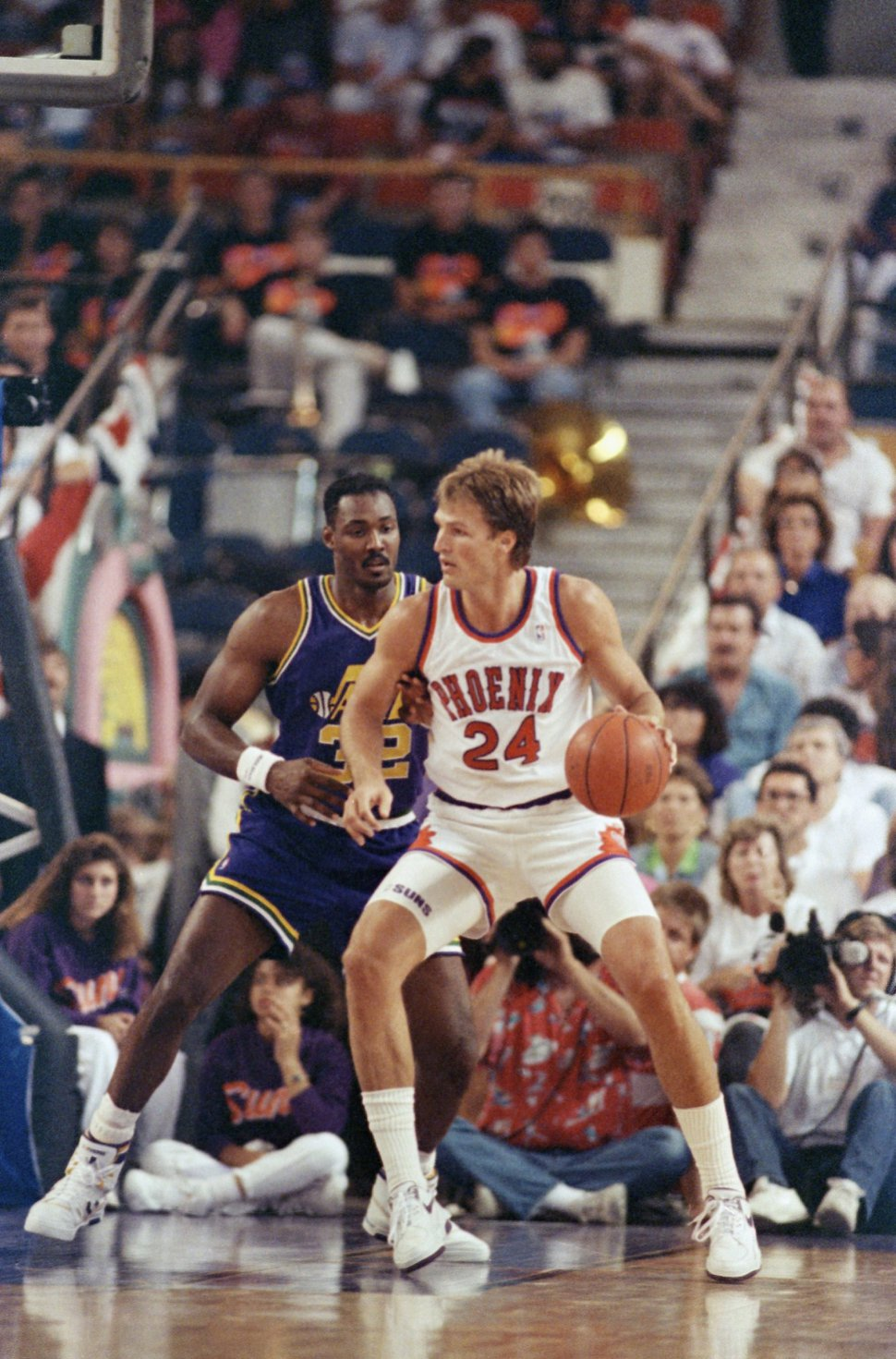 Utah's Karl Malone (left) puts pressure on Phoenix Suns' Tom Chambers (24) during game 4 action in the first round of the NBA Playoffs, Friday, May 5, 1990 in Phoenix. The Jazz defeated Phoenix 105-94 trying the series 2-2. (AP Photo/Jeff Kida)