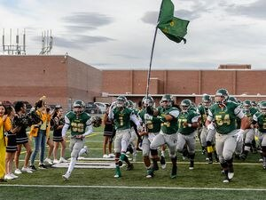 (Trent Nelson | The Salt Lake Tribune)  Kearns players rush onto the field as Kearns hosts Lone Peak, high school football, Thursday September 14, 2017.