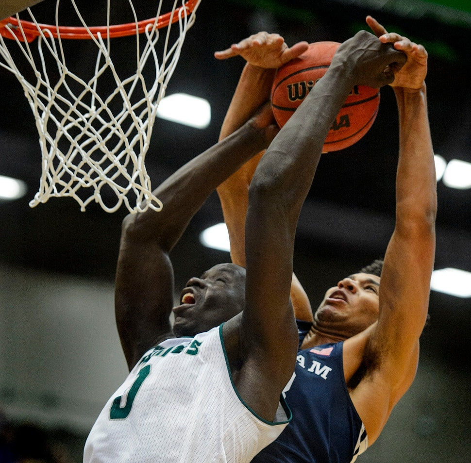 (Steve Griffin | The Salt Lake Tribune) Brigham Young Cougars forward Yoeli Childs (23) blocks a dunk attempt by Utah Valley Wolverines center Akolda Manyang (0) during the BYU versus UVU basketball game at UCCU Center on the UVU campus in Orem Wednesday November 29, 2017.