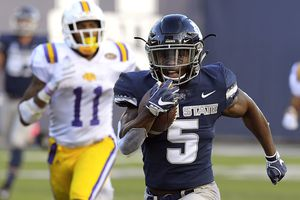 Utah State running back Darwin Thompson (5) carries the ball for a 65-yard touchdown as Tennessee Tech defensive back A.J. Flemister (11) defends during an NCAA college football game, Thursday, Sept. 13, 2018, in Logan, Utah. (Eli Lucero/Herald Journal via AP)