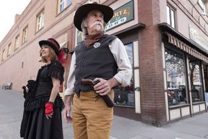 (Jeremy Wade Shockley | Kaiser Health News) Old West actors Cathy Roberts and Scott Perez stand on the lookout for unmasked visitors in Durango, Colorado, on March 21, 2021. Durango doesn't require people to wear masks outdoors but does when people enter any businesses or public buildings.