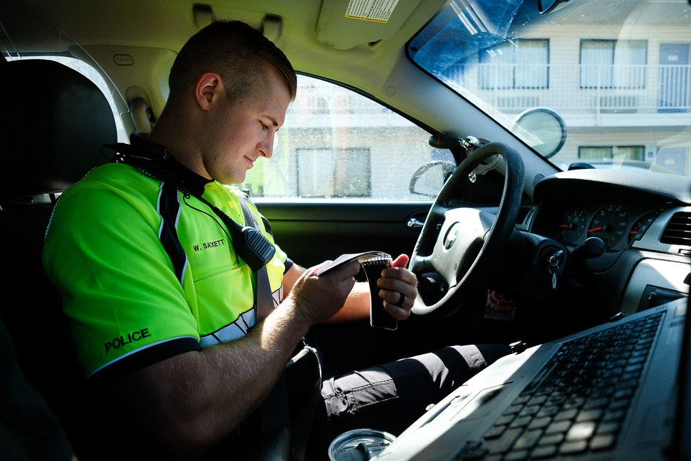 (Francisco Kjolseth | The Salt Lake Tribune) Officer Wyatt Sackett check his notes on a prior arrest as he checks license plates for outstanding warrants while patrolling areas along North Temple in Salt Lake City on Wednesday, Aug. 8, 2018. Members of the west side policing bicycle squad patrol Glendale and Rose Park with an emphasis along North Temple, where they have seen an increase in criminal activity following Operation Rio Grande, now nearing the halfway mark.