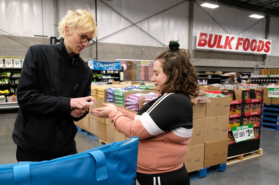 (Francisco Kjolseth   The Salt Lake Tribune) Shandra Benito and Taylor Almond sanitize regularly as they shop for a family at WinCo Foods in Salt Lake City on Wednesday, March 18, 2020, as part of a newly formed Salt Lake Valley COVID Mutual Aid group that connects volunteers with people who need help during the coronavirus outbreak.