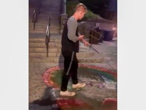 (Screenshot) Captured in a video, a man dumps water on sidewalk chalk art across from Brigham Young University that was meant to support LGBTQ students there on Thursday, August 26, 2021.