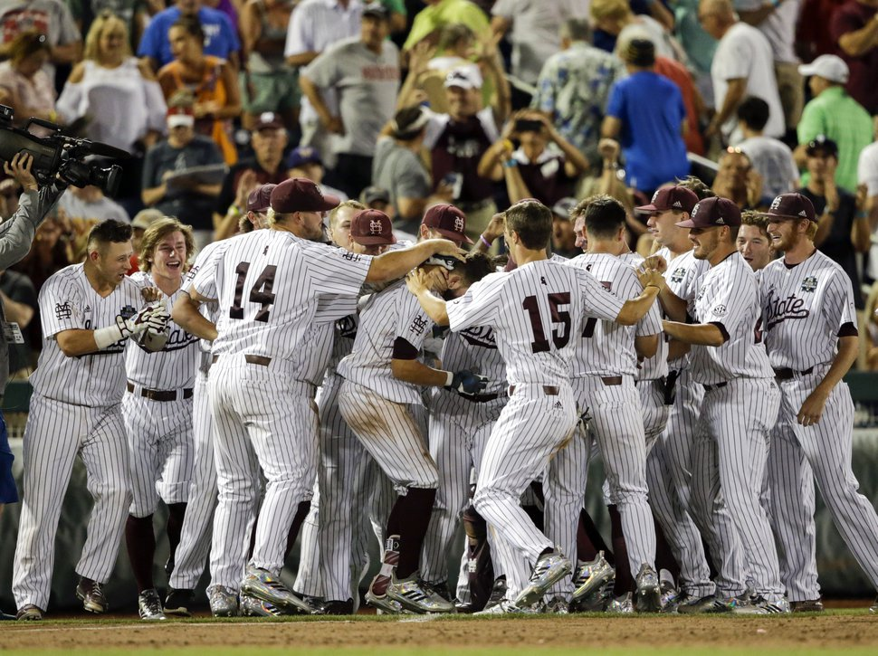 Mississippi State players mob Luke Alexander, center, who hit a single that scored the winning run by Hunter Stovall against Washington in the ninth inning of an NCAA College World Series baseball game in Omaha, Neb., Saturday, June 16, 2018. (AP Photo/Nati Harnik)