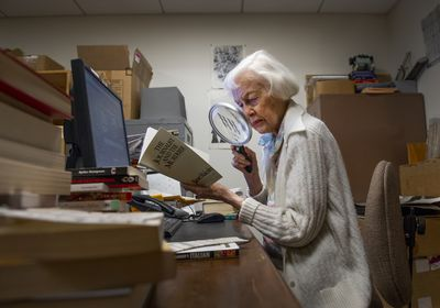 (Leah Hogsten  |  The Salt Lake Tribune)  Lila Weller uses a magnifying glass to help her read as she logs books into a computer at Weller Book Works, August 7, 2019. Weller Book Works - formerly Zion Bookstore and Sam Weller's Books - is celebrating its 90th year.