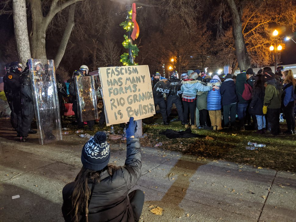 (Paighten Harkins | The Salt Lake Tribune) A protester holds a sign reading,