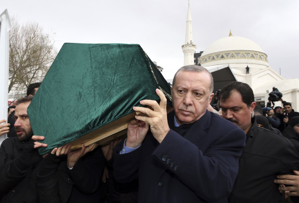 Turkey's President Recep Tayyip Erdogan, center, carries a coffin as he joins hundreds of mourners who attend the funeral prayers for nine members of Alemdar family killed in a collapsed apartment building, in Istanbul, Saturday, Feb. 9, 2019. Erdogan says there are