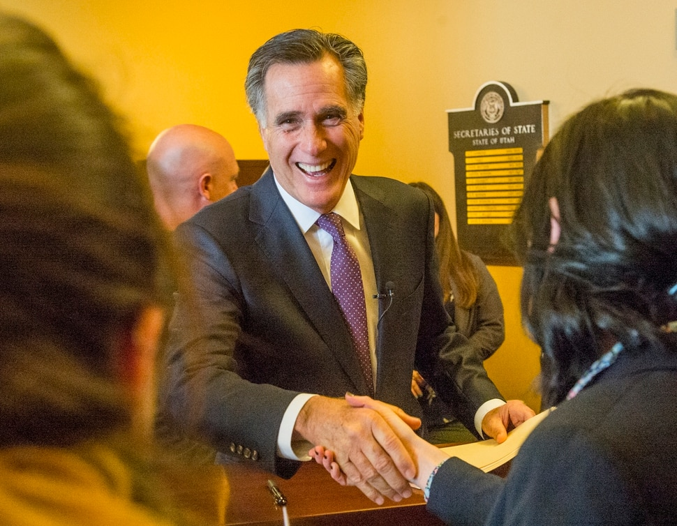 (Rick Egan | The Salt Lake Tribune) Mitt Romney jokes with Election Specialists, Lauren Shafer and Lauren Wilko, as he files to run for the United States Senate, in the Lt. Governor's office at the State Capitol, Thursday, March 15, 2018.