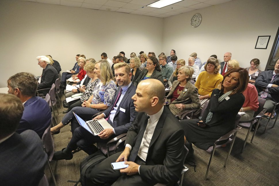 People look on during a hearing Thursday, Sept. 26, 2019, in Salt Lake City. LGBTQ people who say they suffered shame and suicidal thoughts after undergoing gay conversion therapy urged Utah state officials to approve a proposed rule that would prohibit Utah psychologists from the practice that is already banned in 18 states. Opponents who spoke during the hearing countered that the rule should be tabled because they contend it will prevent parents from getting their children help with
