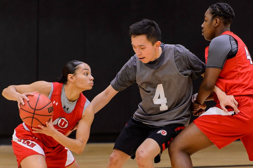 (Trent Nelson | The Salt Lake Tribune) Jerry Li fights through a pick while defending University of Utah guard Kiana Moore drives toward defender Chris Reynolds during a practice session on Wednesday Feb. 13, 2019. Male practice players are a key part of the Utah women's basketball program. At right is Dre'Una Edwards.