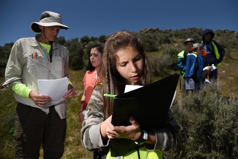 (Francisco Kjolseth | The Salt Lake Tribune) Karlie Lopez, makes sure to complete her documentation of an ancient rock panel at the Adelbert Doyle Smith Family Preserve on the West side of Utah Lake as John McHugh, left, a teacher at Blessed Sacrament Catholic School in Sandy collects the student findings recently. Students at the school are helping document the numerous petroglyphs in the area in an effort to set the archaeological preserve on the National Register of Historic Places.