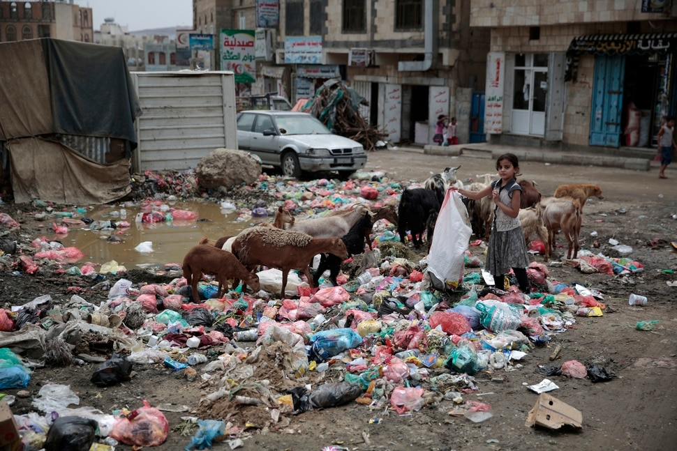 In this photo taken on Wednesday, Jul. 26, 2017, a girl scavenges for recyclable items at a garbage dump in a street in Sanaa, Yemen. Yemen's raging two-year conflict has served as an incubator for lethal cholera. (AP Photo/Hani Mohammed)