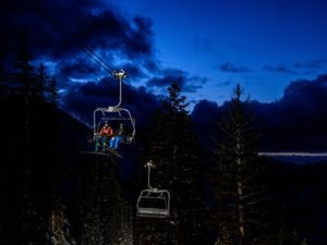 (Trent Nelson  |  The Salt Lake Tribune) Skiers on a lift as night sets in at Brighton on Monday, Feb. 24, 2020.