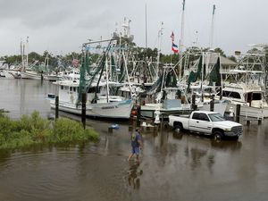Kenny Kuluz wades through flood waters at the Ocean Springs, Miss., harbor as the combination of high tide and the rain bands of Tropical Storm Cindy, dumped rain on the Mississippi Gulf Coast, Wednesday morning, June 21, 2017. (Tim Isbell/The Sun Herald, via AP)