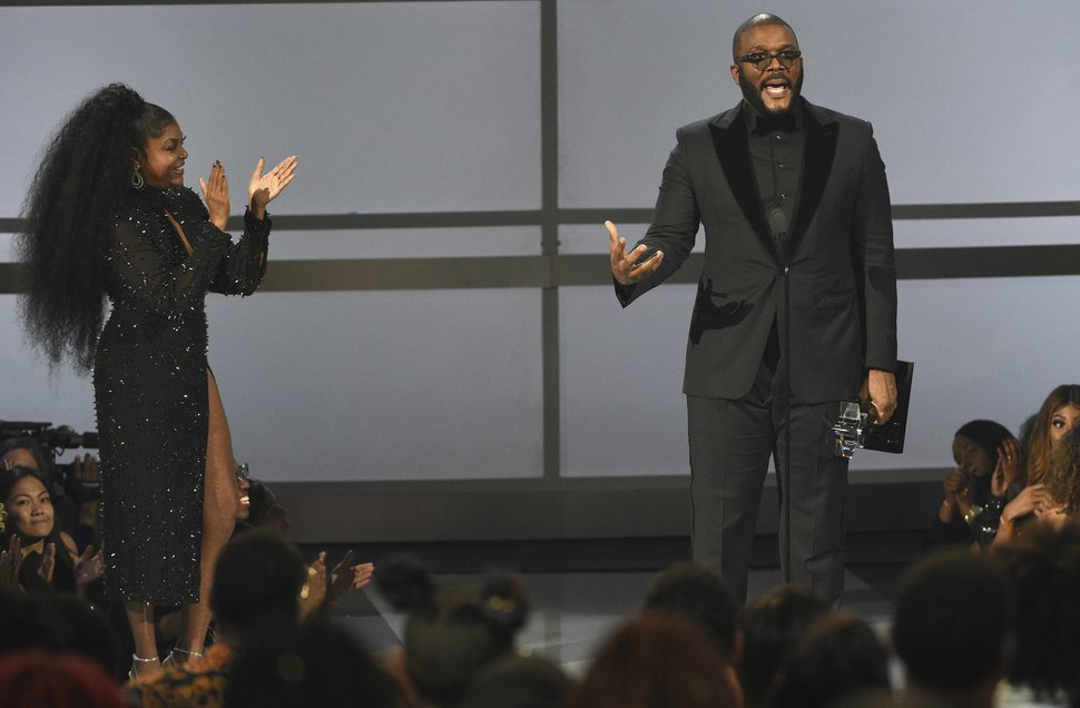 (Chris Pizzello | Invision/AP) Tyler Perry accepts the ultimate icon award at the BET Awards on Sunday, June 23, 2019, at the Microsoft Theater in Los Angeles. Looking on at left is presenter Taraji P. Henson.