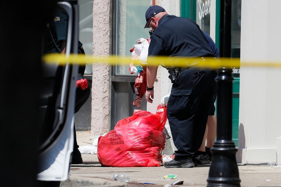 (John Minchillo |AP) Authorities remove bloody rags and debris at the scene of a mass shooting, Sunday, Aug. 4, 2019, in Dayton, Ohio. Multiple people in Ohio have been killed in the second mass shooting in the U.S. in less than 24 hours, and the suspected shooter is also deceased, police said.