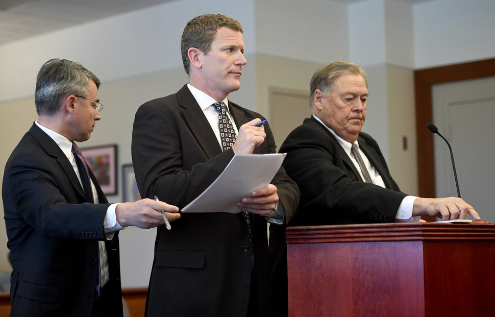 (Pool photo) From left, prosecuting attorney Jacob Taylor hands documents to defense attorney Nathan Crane as he stands beside Gary Anderson during the case of the State v. Anderson on Thursday, May 25, 2017 at the Matheson Courthouse in Salt Lake City.