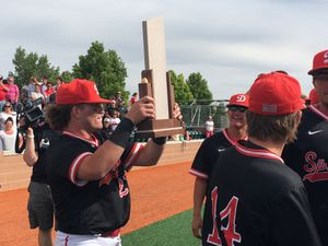 (Eric Butler  |  Special to The Tribune) Spanish Fork senior Hunter Rasmussen takes his turn holding the Class 5A championship trophy after the Dons beat Maple Mountain 14-3 on Saturday.
