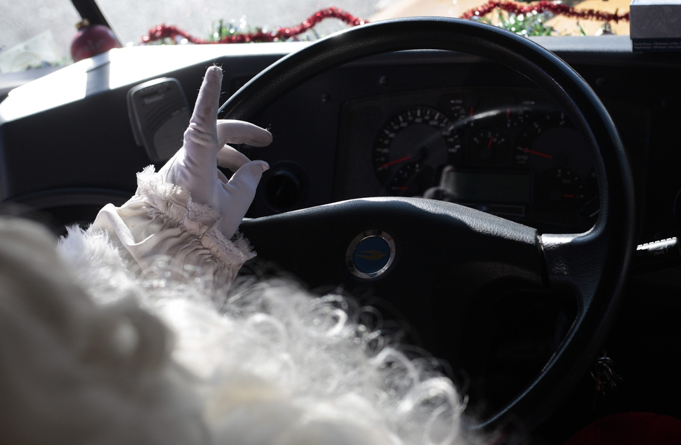 Don Fitch sits at the wheel of bus on Tuesday, Dec. 19, 2017, in American Fork, Utah. Fitch has driven school buses for the Alpine School District for the past four years. Every year around Christmas, he decorates the bus's interior with Christmas decorations, plays Christmas music and dresses up as Santa. (Evan Cobb /The Daily Herald via AP)