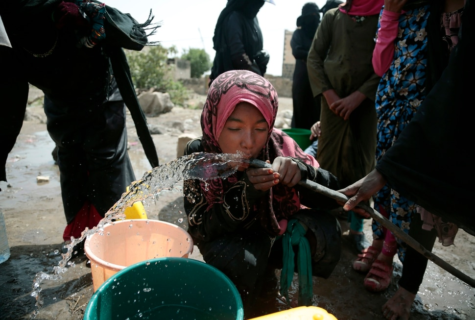 In this photo taken on Wednesday, Jul. 12, 2017, a girl drinks water from a well that alleged to be contaminated water with the bacterium Vibrio cholera, on the outskirts of Sanaa, Yemen. Yemen's raging two-year conflict has served as an incubator for lethal cholera. (AP Photo/Hani Mohammed)