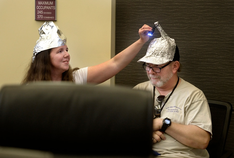 (Scott Sommerdorf | The Salt Lake Tribune) Utah Republican Party Central Committee members Dana Goff, left, helped George Edwards with the light atop his tinfoil hat during a 90 minute debate over what form of voting should be used at the beginning of the Utah Republican Party Central Committee meeting, Saturday, September 9, 2017. Members were split between electronic voting, and old fashioned paper ballots. Voting using paper ballots won out after a demonstration of the electronic voting system failed.