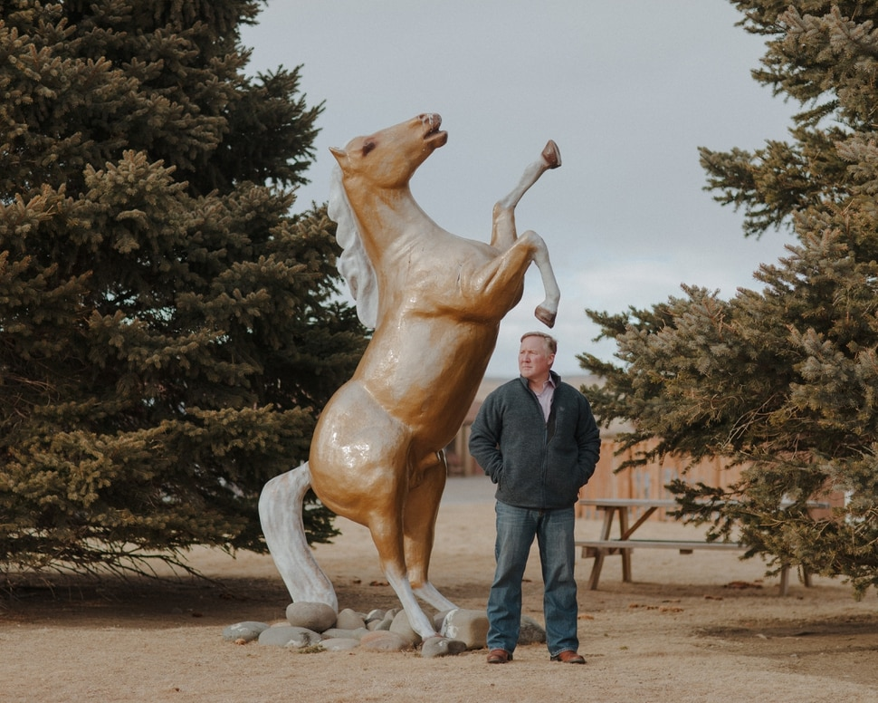 (Elliot Ross | The New York Times) Matt Hall, the mayor of Cody, Wyo., stands with a statue of a horse at the Big Bear Motel in Cody, Jan. 28, 2020. Cody is near Yellowstone National Park, and so its biggest industry is tourism; on summer weekends, its population can grow by about 50 percent, with visitors stopping in to see the rodeo and the nightly recreations of Old West gunfights before heading west to the park.
