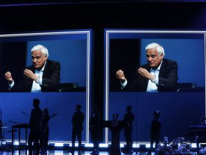 FILE - In this May 29, 2020 file photo, images of Ravi Zacharias are displayed in the Passion City Church during a memorial service for him in Atlanta. A law firm's investigators have released a scathing report on their four-month investigation of alleged sexual misconduct by Zacharias, who founded a global Christian ministry that bears his name. (AP Photo/Brynn Anderson, File)