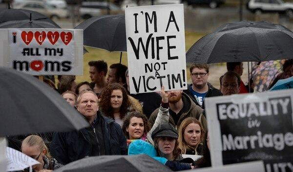 Scott Sommerdorf | The Salt Lake Tribune April Briney, center, a plural wife, holds a sign beside her sister wife Angela Briney, right, blond hair, with other polygamists and their supporters rally on the south steps of the Capitol building, Friday, February 10, 2017.