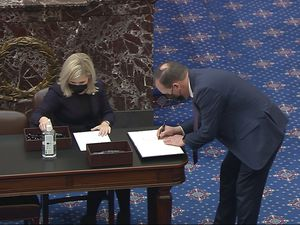 (Senate Television via AP) In this image from video, Sen. Mike Lee, R-Utah, signs the oath book after being sworn in for the impeachment trial of former President Donald Trump in the Senate at the U.S. Capitol in Washington, Tuesday, Jan. 26, 2021.
