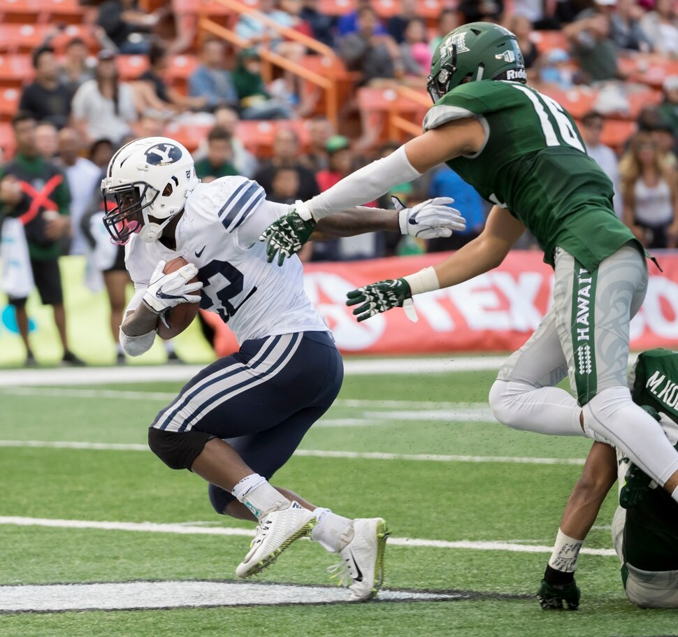 BYU running back Squally Canada, left, scores a touchdown while being defended by Hawaii defensive back Kalen Hicks (16) in the second quarter of an NCAA college football game, Saturday, Nov. 25, 2017, in Honolulu. (AP Photo/Eugene Tanner)