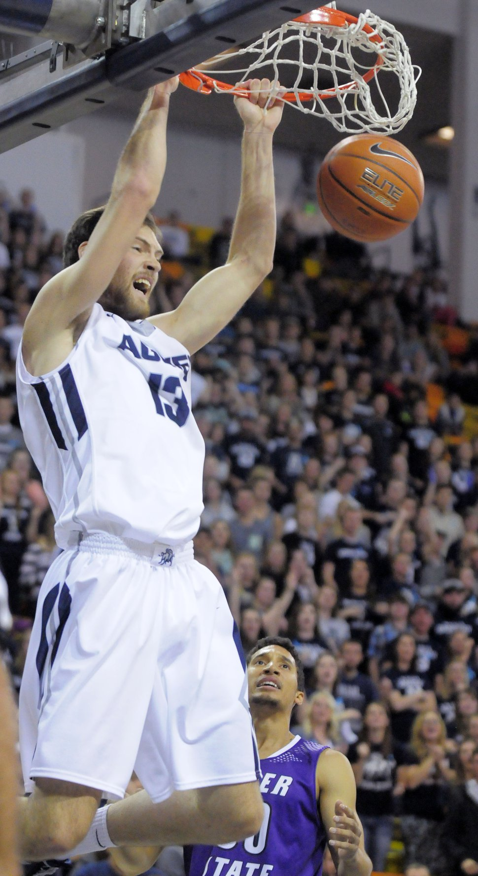 Utah State forward David Collette dunks as Weber State guard Jeremy Senglin watches during an NCAA college basketball game, Friday, Nov. 14, 2014, in Logan, Utah. (AP Photo/The Herald Journal, Eli Lucero)