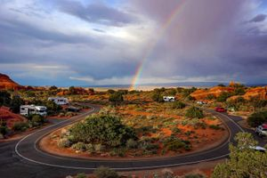 (Francisco Kjolseth  |  The Salt Lake Tribune) The late afternoon sun ignites a rainbow during a brief rain shower in the Devils Garden campground at Arches National Park May 19, 2013.
