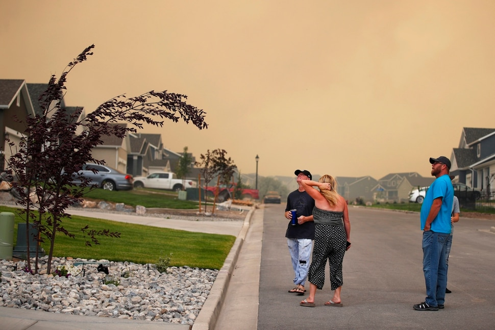 (George Frey | for The Salt Lake Tribune) As high winds bend a tree limb, people watch from their homes in south Saratoga Springs as a nearby wildfire burns on June 28, 2020.