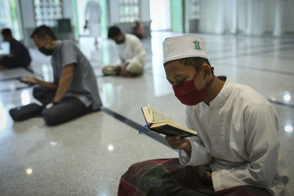 (Heri Juanda | AP file photo) Muslim men wearing face masks as a precaution against the coronavirus read the Quran during the first day of the holy fasting month of Ramadan at a mosque in the religiously conservative province of Aceh, Indonesia, April 24, 2020.