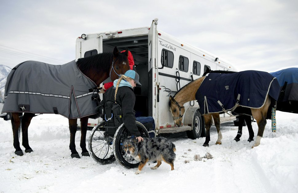 (Isaac Hale | The Daily Herald file photo) In this Jan. 3, 2017, file photo, Amberley Snyder pets her dog Ellie Mae as she and her sister, Autumn Snyder, prepare horses to ride for practice at the Spanish Fork fairgrounds in Spanish Fork. Snyder has no feeling in her legs, but the barrel-racer isn't letting that slow her down.