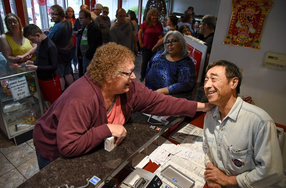 (Francisco Kjolseth | The Salt Lake Tribune) Vicki McMullin, 61, who was ten years old when she started dining at the popular Kowloon Cafe in West Valley City, gives owner Raymond Wang a pat on the back as she recalls fond memories at the establishment. After 60 years in business the restaurant is closing.