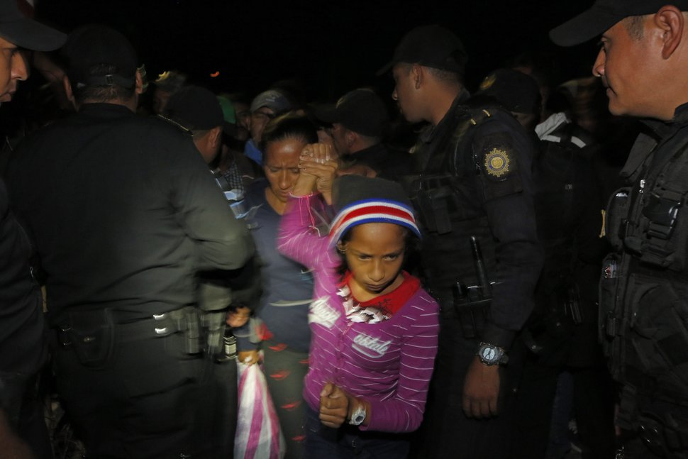 A Honduran migrant family walks between police officers as they enter Guatemala, at the border crossing in Agua Caliente, Guatemala, Tuesday, Jan. 15, 2019. The latest caravan of Honduran migrants hoping to reach the U.S. has crossed peacefully into Guatemala, under the watchful eyes of about 200 Guatemalan police and soldiers. (AP Photo/Moises Castillo)