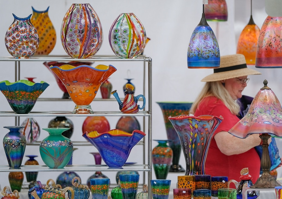 (Francisco Kjolseth | The Salt Lake Tribune) Pamela Allred checks out the works by Hanson & Kastles during the annual 2019 Utah Arts Festival as it kicks off at Library Square and Washington Square in downtown Salt Lake City, Thursday, June 20, 2019, with visual and performance art of all varieties and food for all ages from June 20-23.